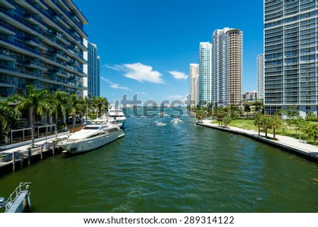 Downtown Miami along the Miami River inlet with Brickell Key in the background and yachts at the dock. - stock photo
