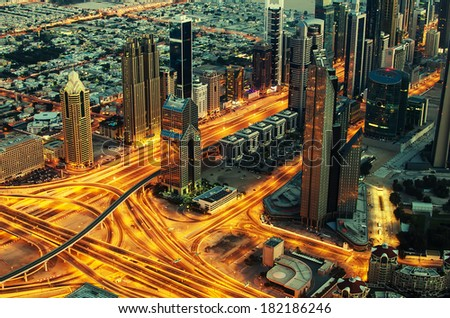 Downtown of Dubai (United Arab Emirates) at night. View from Burj Khalifa, the tallest building in the world. Aerial photo of futuristic cityscape in Arabian Peninsula. Golden lines of modern streets - stock photo
