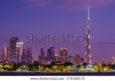 Downtown of Dubai (United Arab Emirates) in the violet arabic sunset. Burj Khalifa, the tallest building in the world. Modern skyscrapers of the city built in the desert. The view from Persian Gulf. - stock photo