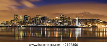 downtown panorama skyline  at dusk cityscape night scene Montreal Canada over river Saint Lawrence impressive and vibrant dusk sky skyscrapers lights reflecting on water surface typical american city - stock photo