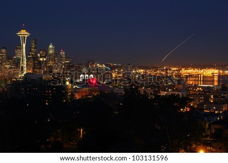 Downtown Seattle at twilight. The Space Needle on the left of frame with Elliott Bay on the right. The streak of light in the sky is a plane landing at the airport. Washington State, USA. - stock photo