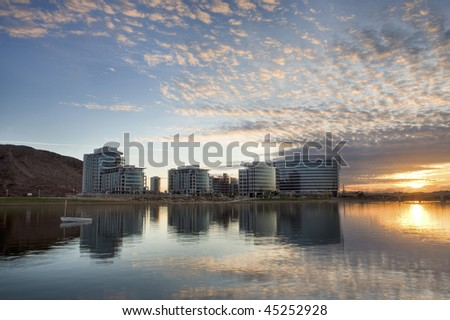 Downtown Tempe office and condo buildings with Tempe Town Lake in the foreground and a fishing boat at sunset. - stock photo