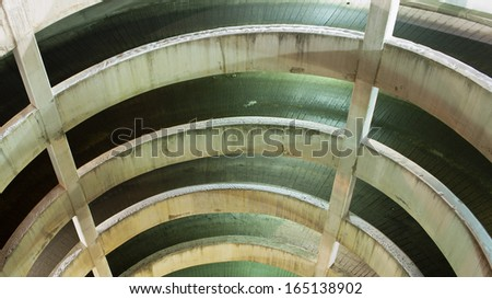 Downward view of a parking lot spiral ramp at night - stock photo