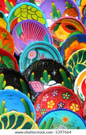 Dozens of handmade bowls are arranged neatly on tables in Chichen Itza Mexico. They are beautifully painted with vibrant colors and unique designs. - stock photo