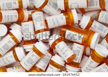 Dozens of prescription medicine bottles in a jumble. This collection of pill bottles is symbolic of the many medications senior adults and chronically ill people take.  - stock photo