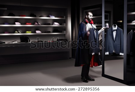 Dracula in a store trying on a suit on sale in the mirror - stock photo