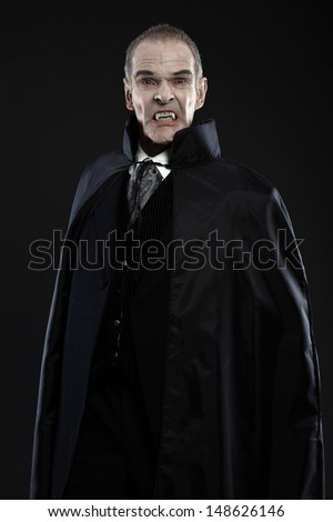 Dracula with black cape showing his scary teeth. Vamp fangs. Studio shot against black. - stock photo