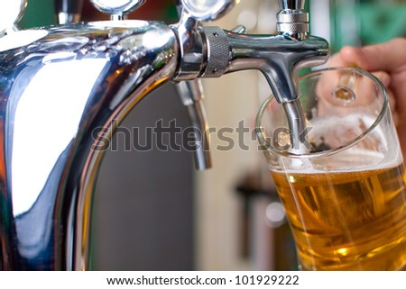 Draft beer pour in a glass from the crane (close-up) - stock photo