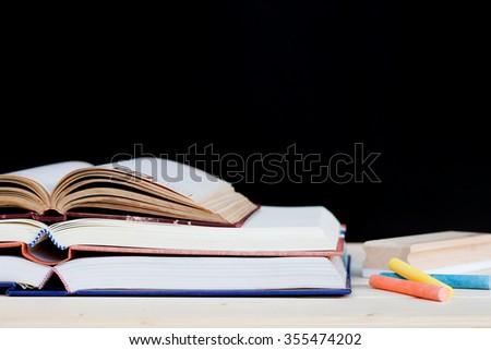 draft, books and chalk to blackboard background - stock photo