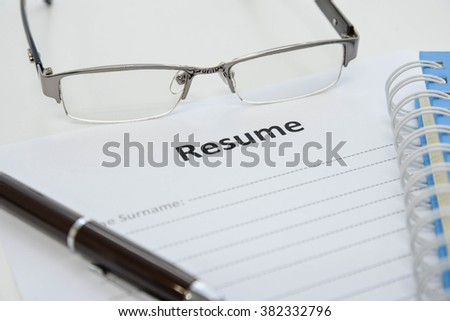 Draft of Resume with pen, notebook and eyeglasses - stock photo