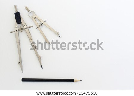 Drafting instruments on a piece of paper. Two pairs of compasses and a pencil are laid out in a symmetrical pattern.