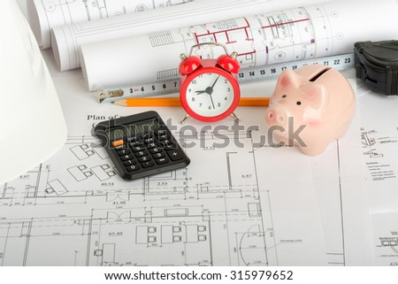 Drafts with piggy bank, calculator and yellow pencil - stock photo