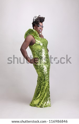 Drag queen wearing a green gown with sequins. - stock photo