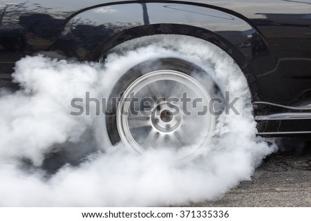 Drag racing car burns rubber off its tires in preparation for the race