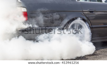 Drag racing car burns rubber off its tires in preparation for the race. - stock photo