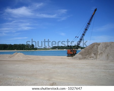 dragline pulling gravel out of water at gravel pit - stock photo