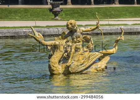 Dragon fountain in beautiful gardens of famous Versailles palace. The Palace of Versailles was a royal chateau. It was added to the UNESCO list of World Heritage Sites. Paris, France. - stock photo