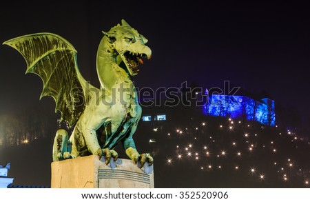 Dragon on the Dragon bridge in Christmas decorated Ljubljana with the cathedral of st. Nicolai in the background at night - stock photo