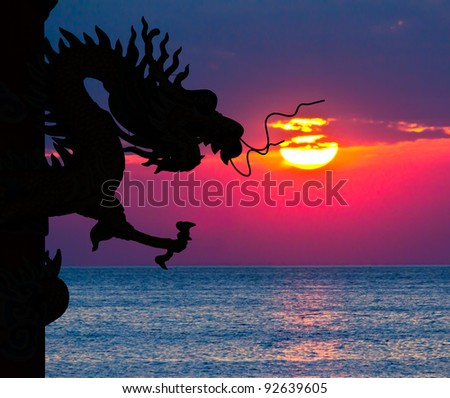 Dragon silhouette and sunset in the sea - stock photo