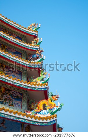 Dragons and ancient animal statue on the roof of Chinese temple with blue sky - stock photo
