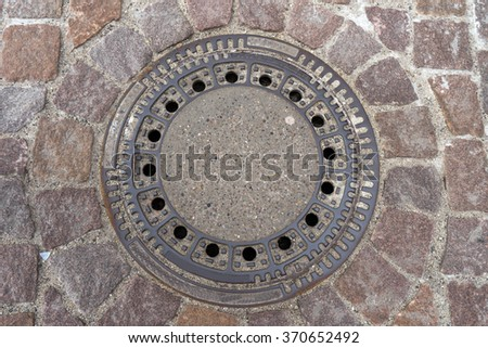 Drain cover on a street / Drain Cover - stock photo