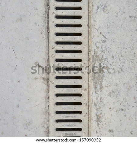 Drain grate in concrete floor as abstract background composition - stock photo
