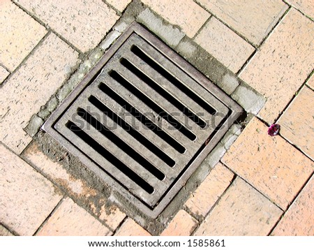 Drain set in footpath - stock photo