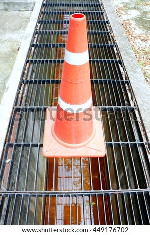Drain water flows down through the steel manhole cover on a sunny spring day  - stock photo