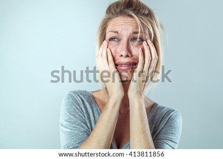 drama concept - discouraged young blond woman in pain with big tears expressing her disappointment and sadness, grey background studio, contrast effects - stock photo