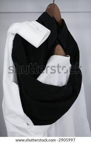 "Drama in a closet. Black shirt tenderly embracing the white shirt, which hides her ""head"" on his chest."