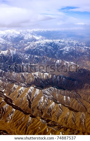 Dramatic aerial view of snoe covered rocky mountains under cloudy sky - stock photo