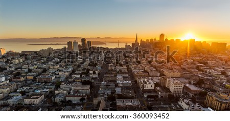 Dramatic aerial view of the sun rising behind San Francisco's financial district - stock photo