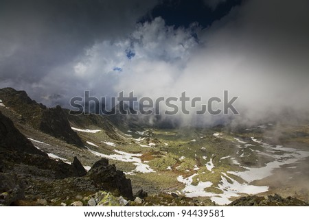 Dramatic alpine scenery with cumulus clouds in high mountains