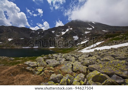 Dramatic alpine scenery with cumulus clouds in high mountains - stock photo