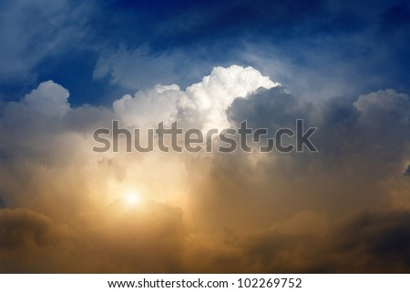 Dramatic background - red sun shines in dark stormy sky - stock photo