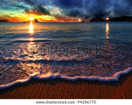 Dramatic beach sunrise with distant building reflection and sea foam - stock photo