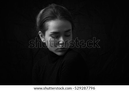 Dramatic black and white portrait of young beautiful girl with freckles in a black turtleneck on black background in studio