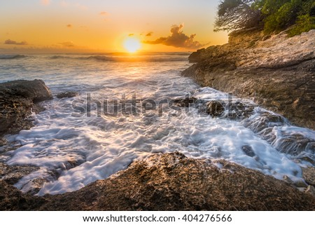 Dramatic Caribbean sunset with stop-action waves and rocky outcrops