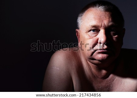 Dramatic close-up portrait of pensive middle aged man - stock photo