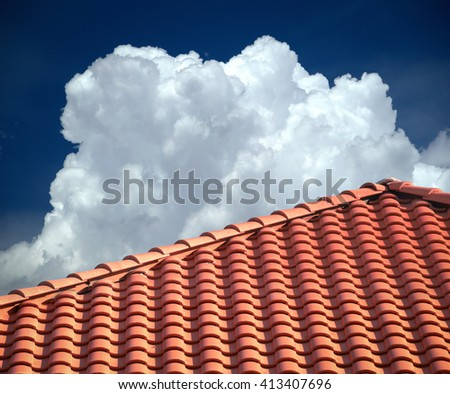 Dramatic cloud formation in a brilliant blue sky over bright red tiled roof. Copy space.  - stock photo