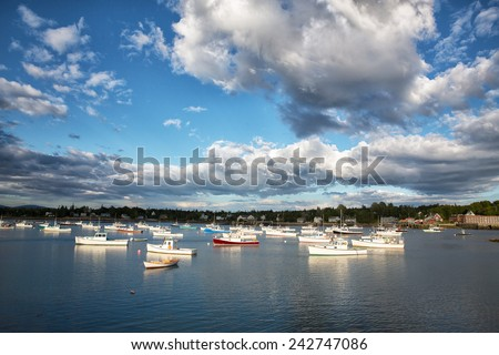 Dramatic cloud formations over small fishing and lobster boats in Southwest Harbor, Mount Desert Island, Maine USA - stock photo