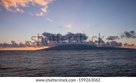 Dramatic clouds and sunset over the beautiful Hawaiian Island of Lana'i - stock photo