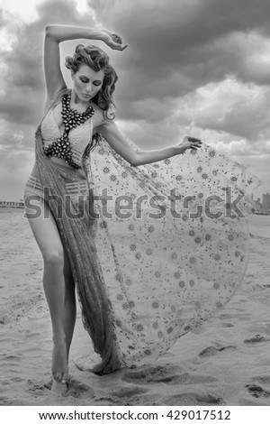 Dramatic clouds at monochrome photos of model walking at empty beach on Coney Island, Brooklyn NY - stock photo