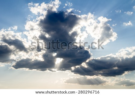 Dramatic clouds on blue sky with sun rays - stock photo
