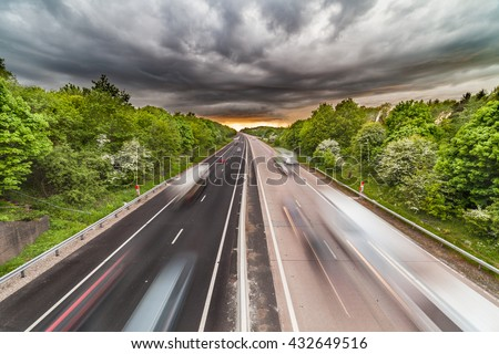 Dramatic Clouds over Busy Motorway with Vehicles in Motion