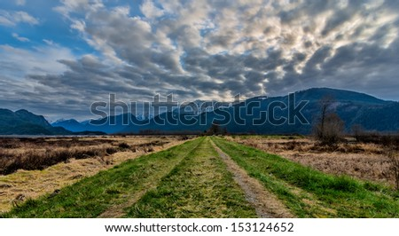 Dramatic clouds with grass road leading to mountains - stock photo