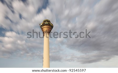 Dramatic cloudscape sky floating in motion over an airport control tower for the concept of aviation guidance beacon. - stock photo