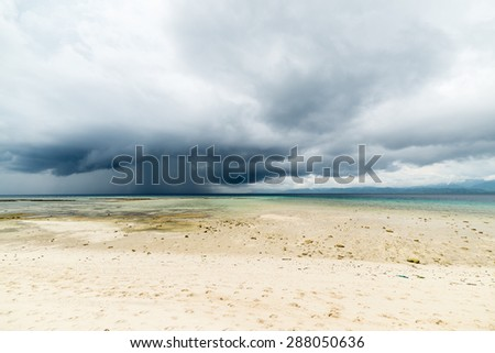 Dramatic cloudscape with heavy rain and tropical storm at the horizon on the coastline of Tanjung Karang, Central Sulawesi, Indonesia. Wide angle shot frome the coral spotted white sandy beach.  - stock photo