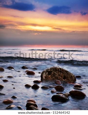 Dramatic colorful sunrise on a rocky beach. Baltic sea - stock photo