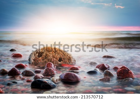 Dramatic colorful sunset on a rocky beach. Baltic sea. Seascape theme - stock photo